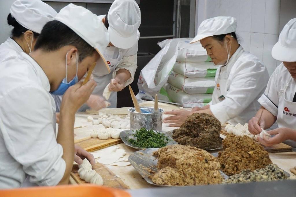 people preparing dumplings for lunch