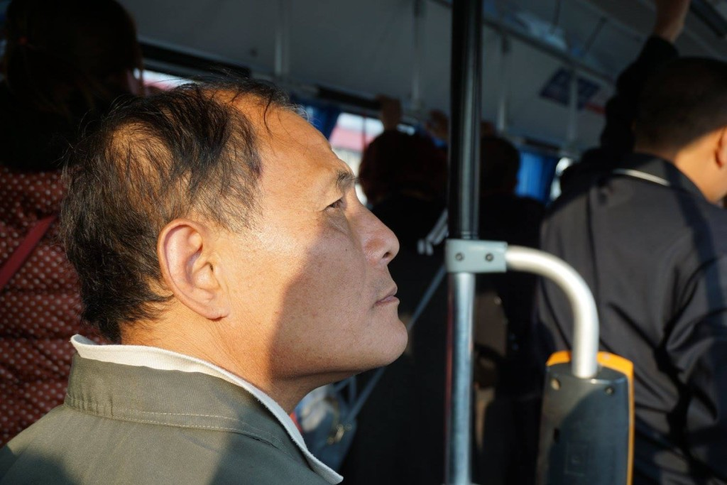 A very calm man on a very hectic bus.