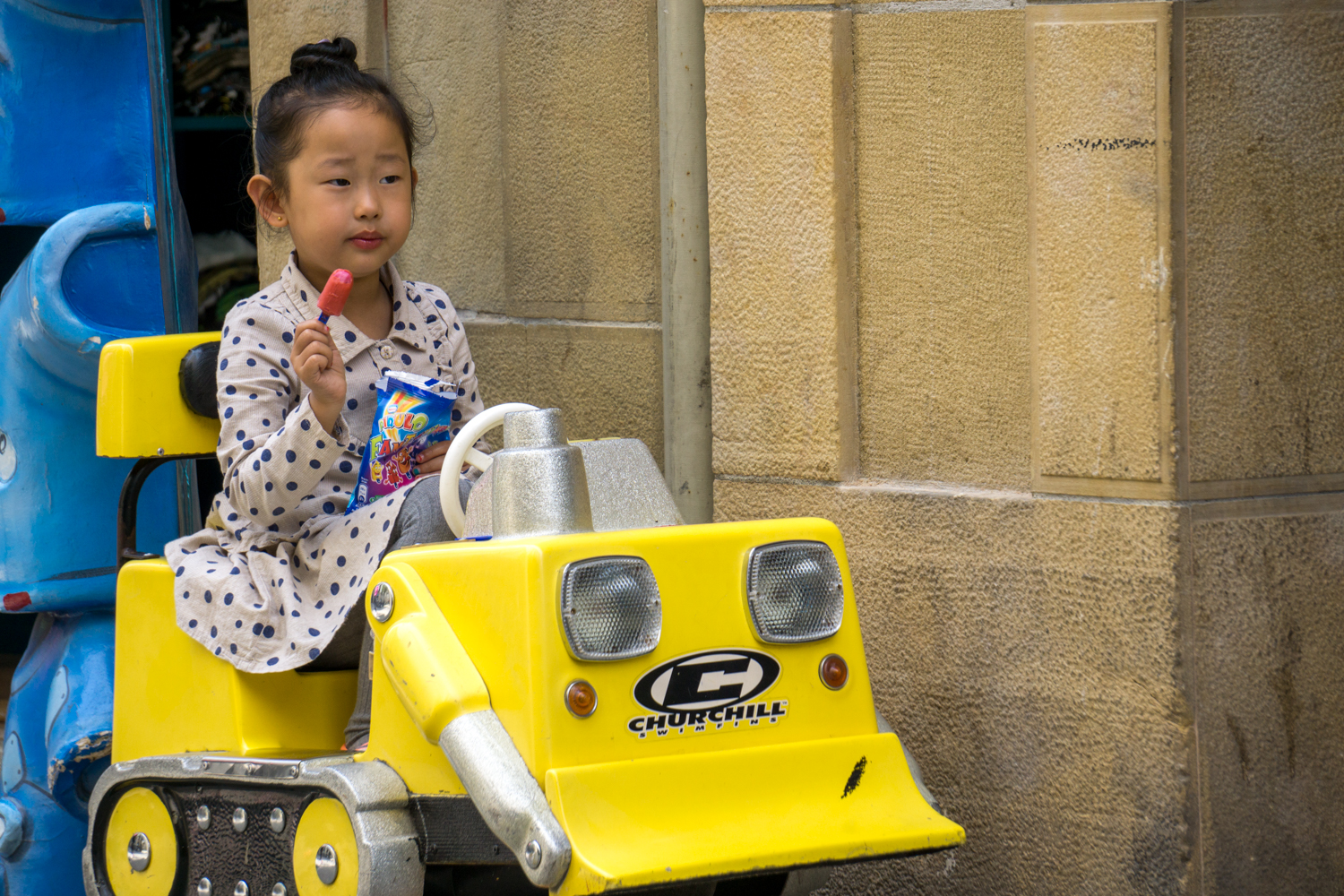 A young girl enjoys a snack and a drive in San Sebastián.