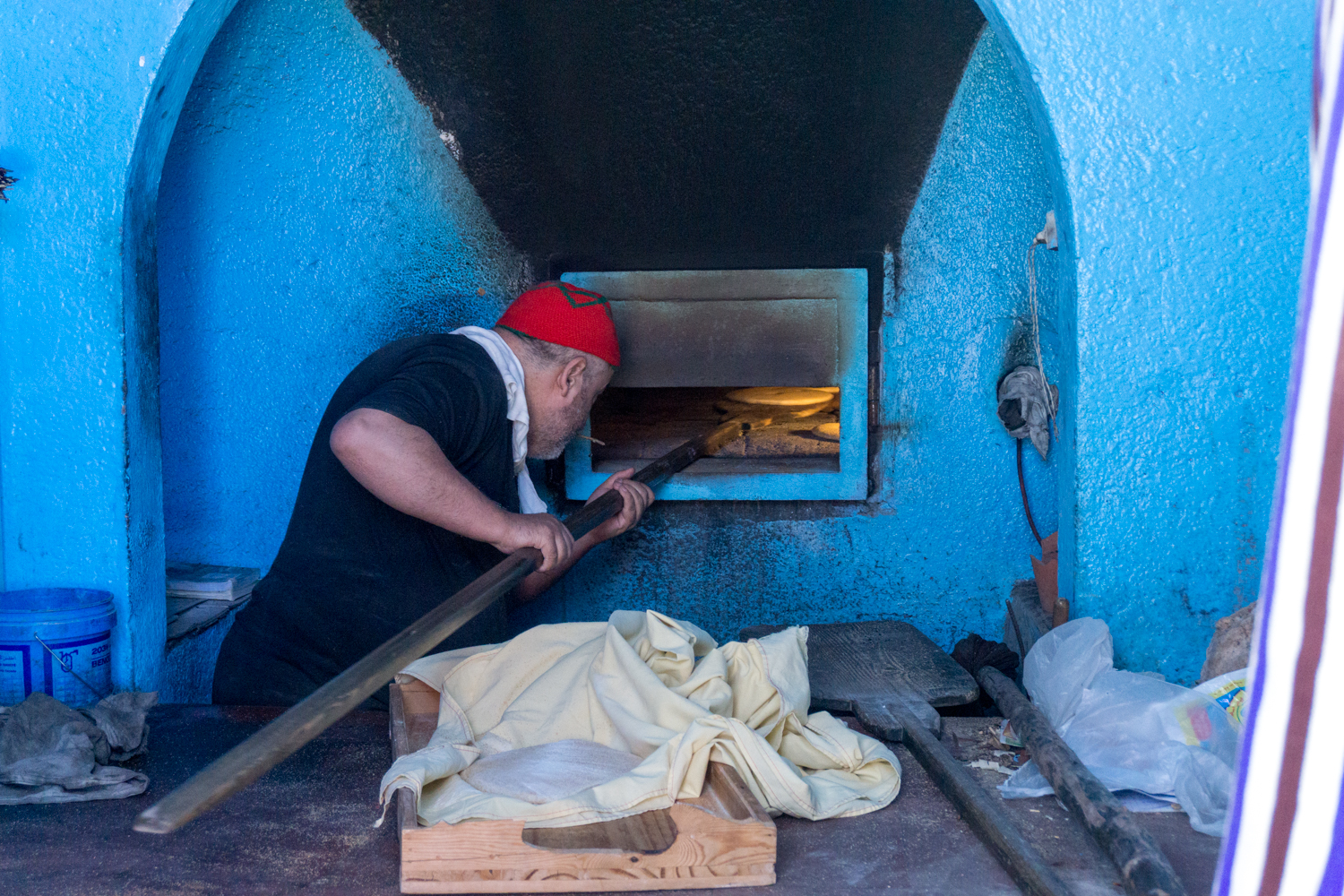 A baker in Chefchaouen making some bread in a wood burning oven.